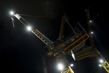 Building construction tower crane yellow cabin at night lighted with spotlight from low angle