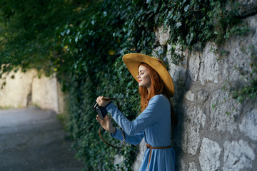 Young beautiful woman in a blue dress walking along the street with a camera