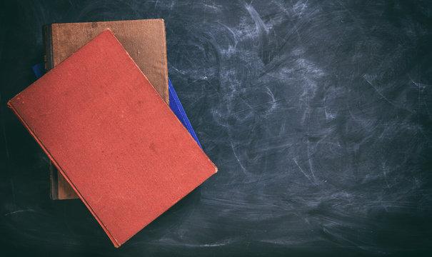 Vintage books on a blackboard - copy space