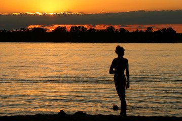 Woman poses for a picture during sunset on the beach along the Volga river in Samara