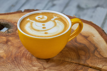 Latte cup with snowman art. Coffee drink on wood board.