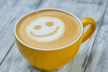 Smiley latte art. Yellow coffee cup close up. Does caffeine make you happy.