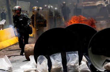 Security forces take position during clashes at a rally against Venezuelan President Maduro's government in Caracas
