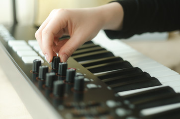 woman adjusts the synthesizer
