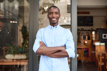 Smiling African entrepreneur standing outside of his trendy cafe