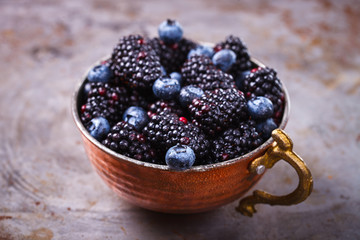 Berry Fresh in a copper cup on the Metal Background. Blackberries,Blueberry.Food or Healthy diet concept.Super Food.Vegetarian.Copy space for Text.selective focus.