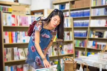 Asian girl choosing book in a bookstore