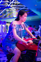 Girl on toy motorbike in an arcade
