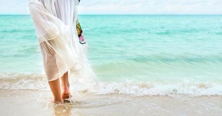 Girl walking to the sea wearing white dress