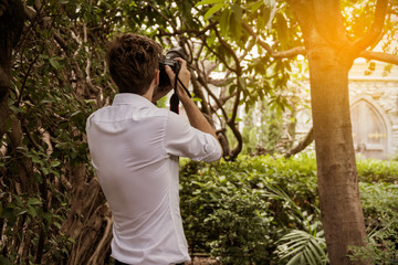 The back of the photographer is taking picture in the garden. Vintage tone