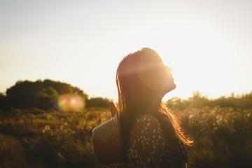 Beautiful hippie girl walking down the meadow field