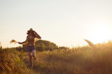 Young woman running down the meadow field