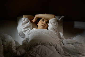 Woman with insomnia lying in bed with open eyes