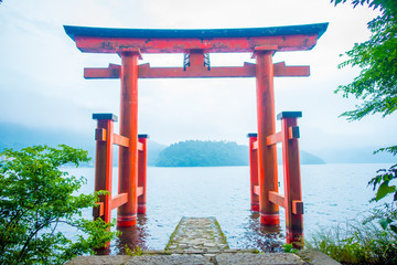Bright red Torii gate submerged in the waters of Ashi lake, caldera with mountains on the background. Hakone Shrine, Kanagawa prefecture, Japan