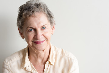 Portrait of beautiful older woman with short grey hair and blue eyes against neutral background (selective focus)