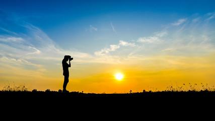 Photographer man shooting on sunset