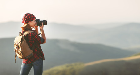 Woman tourist photographer with camera on top of mountain at sunset  a hike in summer
