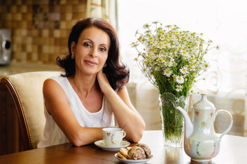 Beautiful old woman in a white blouse sitting at a round table with a bouquet of daisies ,smiling and drinking coffee with biscuits in the kitchen .Lovely housewife