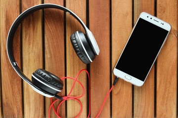 Headphones  on wood background ,Concept listen to music from smartphone