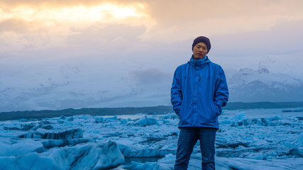 Asian man stand in front of million years old iceberg at glacier lagoon Iceland