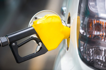 White car being filled with fuel at the gas station