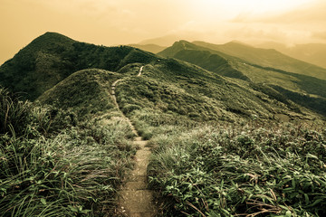 Tuinposter Heuvel Storybook landscape of a footpath through rolling hills on the Caoling Historic Trail in Taiwan