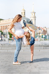 Mother and daughter doing exercise outdoors. Pregnant woman helps her little girl to stretch. Healthy lifestyle. Yoga. Girl gymnast stretching on the street. The girl is engaged in gymnastics.