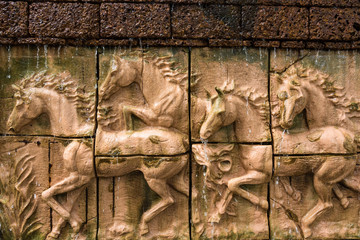 Stone sculpture of horse on brick wall with waterfall.