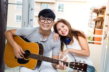 Asian woman love to listen at a man who is singing and playing a guitar.