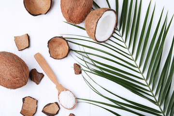 Coconuts with flakes in spoon on white wooden table
