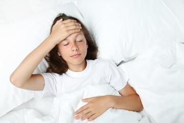 Sick girl lying in white bed