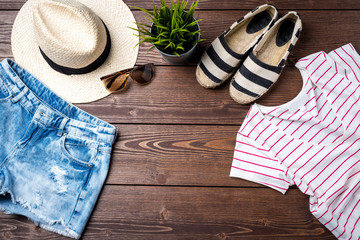 Casual female clothes on wooden background. Top view