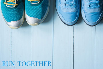 two pairs of running sneakers on blue background