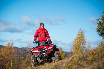 Bottom view. A guy on the red ATV quad bike against blue sky in the autumn landscape nature. Sunny day in the mountains