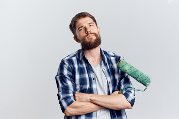 Young guy with a beard on a white isolated background holds a building roller, repairs