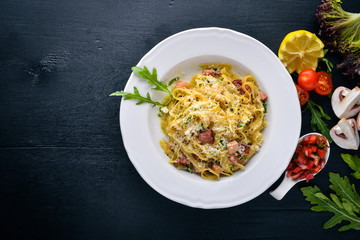 Pasta with bacon, cherry tomatoes, olives, and mushrooms with parmesan cheese. Italian food. On a black wooden surface. Free space for your text. Top view.