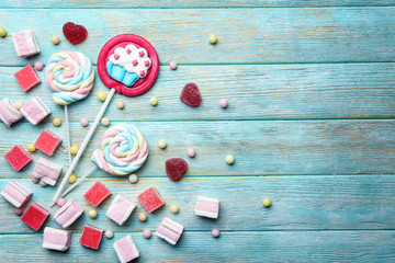 Composition of delicious candies on blue wooden table