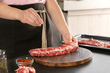 Professional cooker spicing fresh juicy spare ribs on table