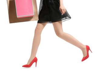Young woman with beautiful legs carrying shopping bags on white background