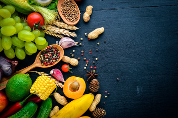 A large selection of raw vegetables, fruits and spices on a black wooden surface. Free space for your text. Top view.