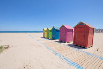 five wooden bathing cabins or huts, colored in blue, red, pink, yellow and green, and wooden footway on sand, Beach of PIne or Pinar, Grao Castellon, Valencia, Spain, Europe. Blue sky