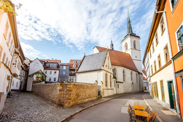 Beautiful street view with colorful buildings and church tower in the old town of Erfurt city during the morning light in Germany