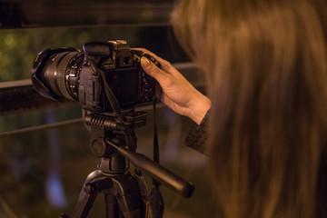 Young woman looking at camera display at night, closeup