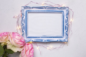 Empty photo frame, flowers  and fairy lights on grey textured background. Top view. Flat lay. Place for text. Mock up.