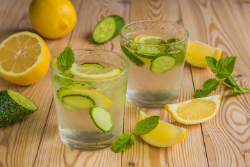 Detox water, fresh organic lemonade with ice, cucumber, lemon and mint on wooden background