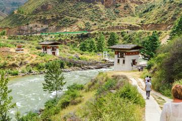 People walking towards the Iron Bridge of Tamchog Lhakhang Monastery, Paro River, Bhutan.