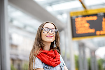 Portrait of a young woman waiting for the public transport standing on the tram stop with timetable on the background