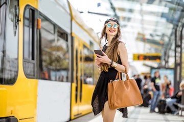 Lifestyle portrait of a stylish woman in black dress and hat standing with bag and phone on the tram stop in the modern city