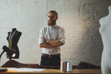 Bearded man standing in atelier looking away