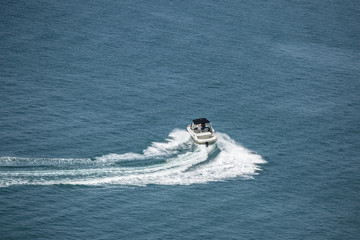 high speed motor boat with wave trail on the water.